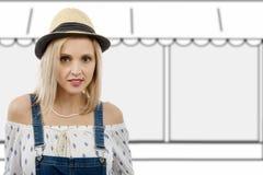 Schöne blonde Frau, die mit Sommerhut aufwirft Lizenzfreies Stockfoto