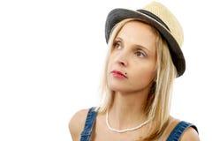 Schöne blonde Frau, die mit Sommerhut aufwirft Lizenzfreie Stockbilder
