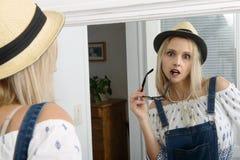 Schöne blonde Frau, die mit Sommerhut im Spiegel aufwirft Stockbilder