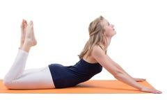 Schöne blonde Frau, die Muskeln der Rückseite, Beine, Hüften, Hinterteile ausdehnend auf einer Matte tut Lizenzfreie Stockfotos