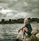 Schöne blonde Frau, die nahe dem Wasser sitzt Stockbilder