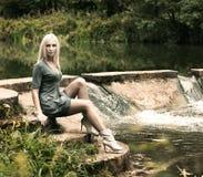 Schöne blonde Frau, die nahe dem Wasserfall sitzt Lizenzfreies Stockfoto
