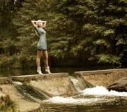 Schöne blonde Frau, die nahe dem Wasserfall steht Stockfotos