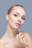 Schöne blonde Frau, die rosa Lipgloss auf grauem Hintergrund hält Lippenmake-up Stockbilder