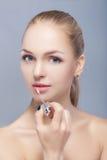 Schöne blonde Frau, die rosa Lipgloss auf grauem Hintergrund hält Lippenmake-up Lizenzfreies Stockfoto
