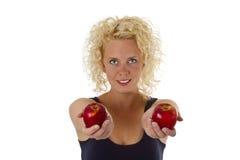 Schöne blonde Frau, die rote Äpfel anhält Stockfotografie