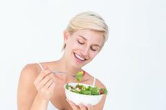 Schöne blonde Frau, die Salat isst Lizenzfreie Stockbilder
