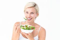 Schöne blonde Frau, die Salat isst Stockfoto