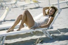 Schöne blonde Frau, die sich auf einem Klappstuhl hinlegt Stockfotografie