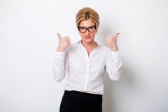 Schöne blonde Frau, die sich Daumen zeigt Stockbild