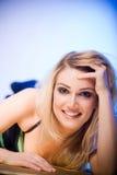 Schöne blonde Frau, die sich vorwärts lehnt Stockbild