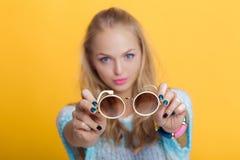 Schöne blonde Frau, die Sonnenbrille auf gelbem Hintergrund hält Fokus auf den Gläsern Stockfoto