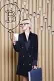 Schöne blonde Frau, die stehende nahe bitcoin Skizze zeigt Virtuelles Geld- oder btczerstampfungskonzept Cryptocurrency Lizenzfreie Stockfotografie