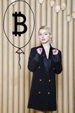 Schöne blonde Frau, die stehende nahe bitcoin Skizze zeigt Virtuelles Geld- oder btczerstampfungskonzept Cryptocurrency Stockfotografie