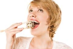 Schöne blonde Frau, die Sushi isst. Studio Stockfotografie