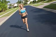 Schöne blonde Frau, die in Vorstadtstraße läuft Stockfotos