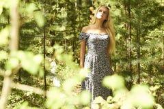 Schöne blonde Frau, die in Wald geht. Sommer Stockfoto