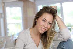 Schöne blonde Frau, die zu Hause sitzt Stockbilder
