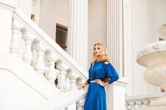 Schöne blonde Frau draußen auf der Treppe Stockfoto