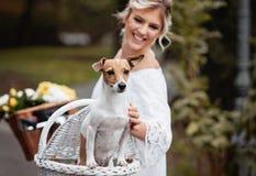 Schöne, blonde Frau draußen in einem Park mit einem Schoßhund Stockfotos