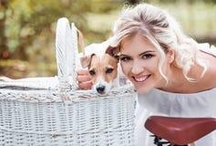 Schöne, blonde Frau draußen in einem Park mit einem Schoßhund in einem Korb Stockfotografie