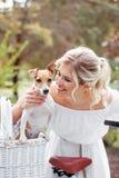 Schöne, blonde Frau draußen in einem Park mit einem Schoßhund in einem Korb Stockfoto