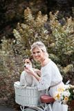 Schöne, blonde Frau draußen in einem Park mit einem Schoßhund in einem Korb Lizenzfreies Stockbild