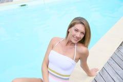 Schöne blonde Frau durch den Swimmingpool Lizenzfreies Stockfoto