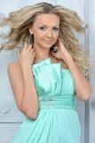 Schöne blonde Frau in einem blauen Kleid. Stockbilder