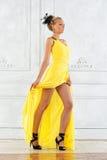 Schöne blonde Frau in einem gelben Kleid. Stockbild
