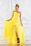 Schöne blonde Frau in einem gelben Kleid. Stockbilder