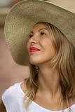 Schöne blonde Frau in einem Hut, der oben mit den roten Lippen in einem weißen T-Shirt schaut Lizenzfreie Stockfotos