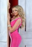 Schöne blonde Frau in einem rosafarbenen Kleid. Stockfotos
