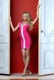 Schöne blonde Frau in einem rosafarbenen Kleid. Lizenzfreies Stockfoto