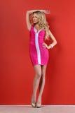 Schöne blonde Frau in einem rosafarbenen kurzen Kleid. Lizenzfreie Stockfotografie