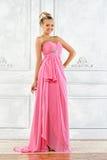 Schöne blonde Frau in einem rosafarbenen langen Kleid. Lizenzfreie Stockfotos