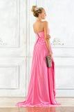 Schöne blonde Frau in einem rosafarbenen langen Kleid. Lizenzfreies Stockfoto