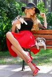 Schöne blonde Frau in einem schwarzen Hut mit den langen Beinen, die auf einer Bank hält die nette Katze sitzen Lizenzfreie Stockbilder
