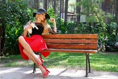 Schöne blonde Frau in einem schwarzen Hut mit den langen Beinen, die auf einer Bank hält die nette Katze sitzen Stockfotos