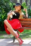 Schöne blonde Frau in einem schwarzen Hut mit den langen Beinen, die auf einer Bank hält die nette Katze sitzen Lizenzfreies Stockfoto