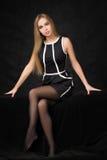 Schöne blonde Frau in einem schwarzen Kleid auf einer Dunkelheit Lizenzfreies Stockbild
