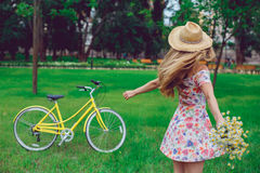 Schöne blonde Frau in einem Strohhut auf einem Rasen mit Blumen wirbelt und tanzt in den Park Lizenzfreie Stockbilder