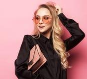 Schöne blonde Frau in einer Bluse und in Hosen, welche die Gläser, Handtasche halten tragen Stockbilder