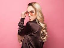Schöne blonde Frau in einer Bluse und in Hosen, welche die Gläser, Handtasche halten tragen Lizenzfreie Stockfotos