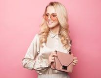 Schöne blonde Frau in einer Bluse und in Hosen, welche die Gläser, Handtasche halten tragen Lizenzfreies Stockfoto