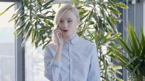 Schöne blonde Frau geht und spricht am Telefon im Büro stock footage