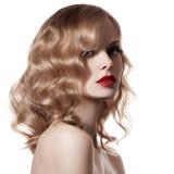 Schöne blonde Frau. Gelocktes Haar. Weißer Hintergrund Stockfotos