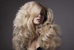 Schöne blonde Frau. Gelocktes langes Haar Lizenzfreies Stockfoto