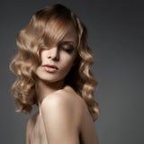 Schöne blonde Frau. Gelocktes langes Haar Lizenzfreie Stockfotografie