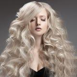 Schöne blonde Frau. Gelocktes langes Haar Stockfotografie